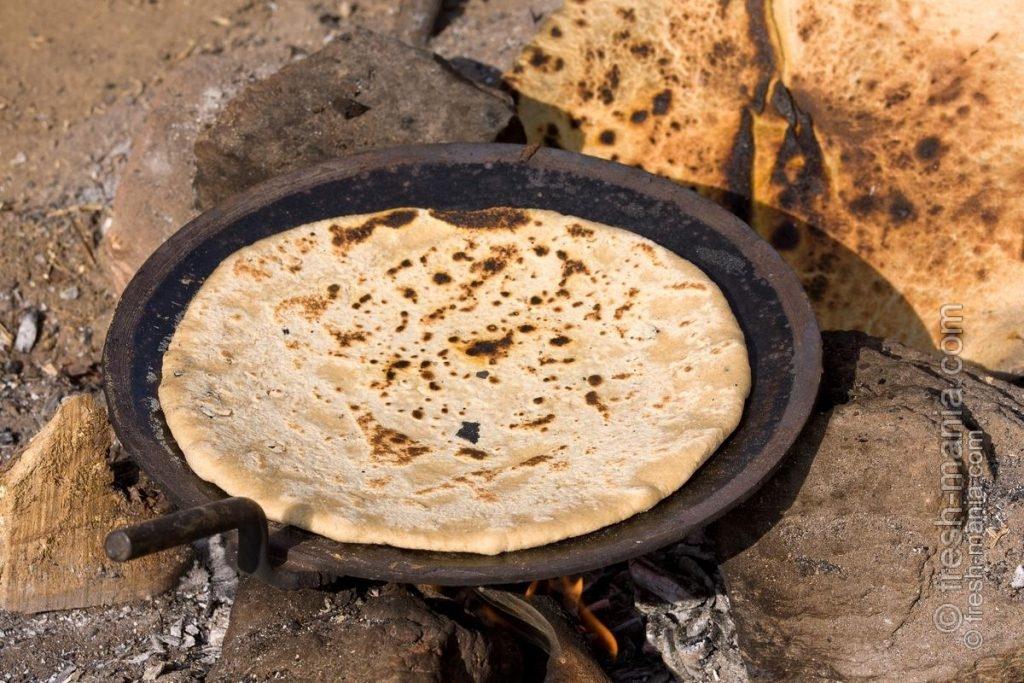 Чапати пекут на разгоряченной поверхности, затем на открытом огне